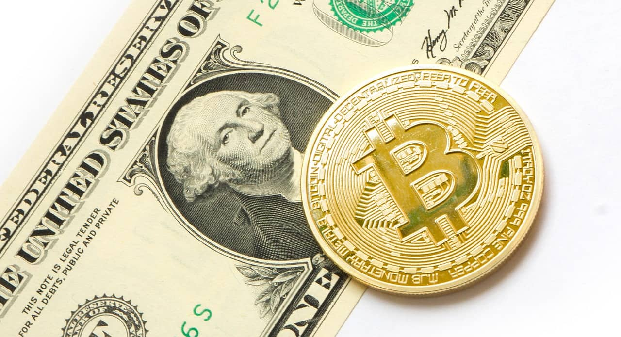 Bitcoin physical coin lies on dollar note